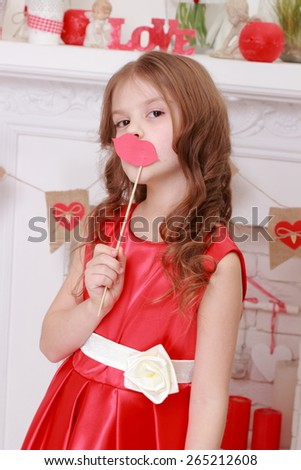 Charming cheerful little girl with beautiful hair in red dress on Valentine's Day - stock photo
