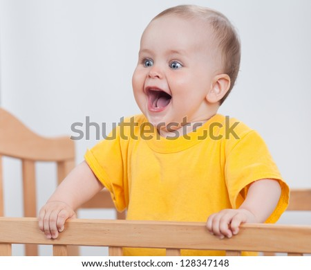 Charming child in the crib. Charming baby in yellow holds the handrails and laughs - stock photo