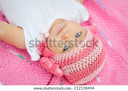 Charming child. Little girl in white knitted bear hat  - stock photo