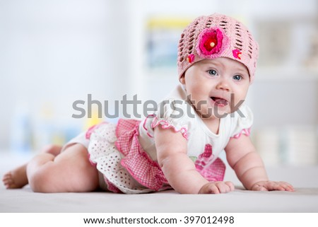 Charming child little girl with hat lying on her stomach - stock photo