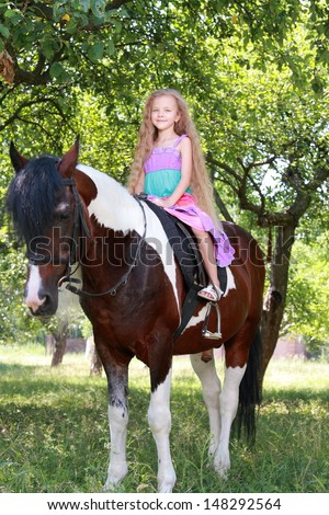 Charming child with a sweet smile sitting astride a ponies/Beautiful ponies eats green grass in a summer park