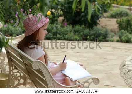 Charming concentrated little girl draws on the album to draw sitting in the summer park outdoors on bench - stock photo