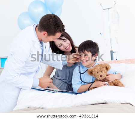 Charming doctor playing with a little boy and his mother at the hospital - stock photo
