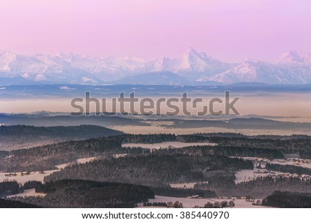 Charming early morning view of colored peaks of the Alps from 80 km away Dreisessel in Bavaria, GERMANY.