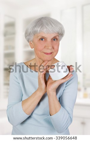 charming elderly woman applying cosmetic cream on her face for facial skin care in bathroom at home