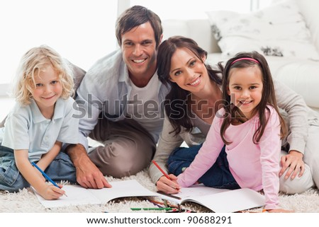 Charming family drawing together in a living room - stock photo