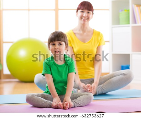 Charming family kid and mother spend time in the gym