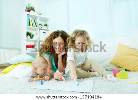 Charming family of three spending their weekend at home drawing - stock photo