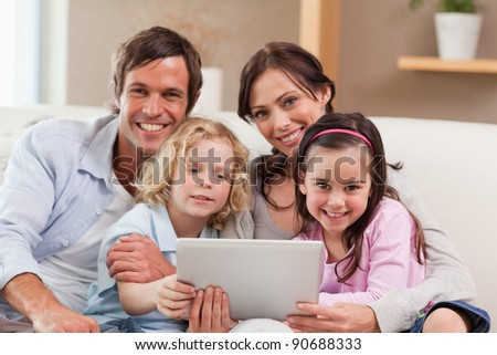 Charming family using a tablet computer in a living room - stock photo