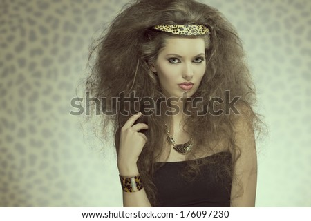 charming fashion brunette lady with long curly brown hair-style, pretty make-up and leopard accessories and necklace.  - stock photo