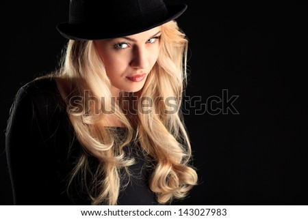 Charming fashion model posing over black background.