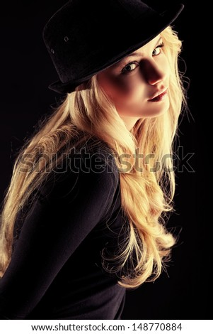Charming fashion model posing over black background. - stock photo