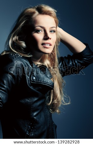 Charming fashion model posing over dark background. - stock photo