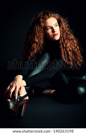 Charming fashion model with beautiful curly hair posing at studio. Over black background.