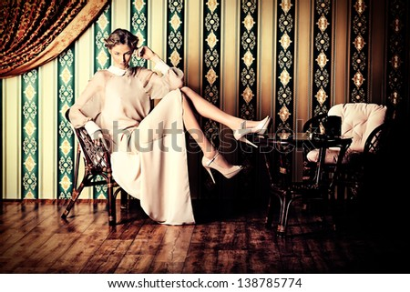 Charming fashionable model posing in the vintage interior. - stock photo