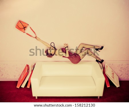 Charming fashionable woman flying over the sofa in the room with her bag. Sepia. - stock photo