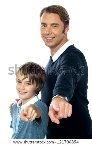Charming father and son pointing at you posing sideways. White background.