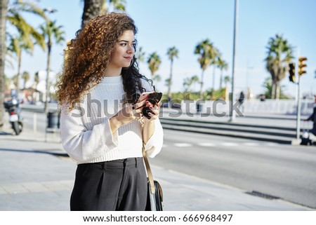 Charming female tourist enjoying good spring weather while strolling on streets using application for navigating searching right direction, attractive travel with curly hair resting during city tour