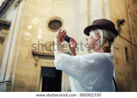 Charming female with funky look making photo on cell telephone while standing near architectural monument in urban setting, woman traveler photographing on mobile phone interesting objects outdoors - stock photo