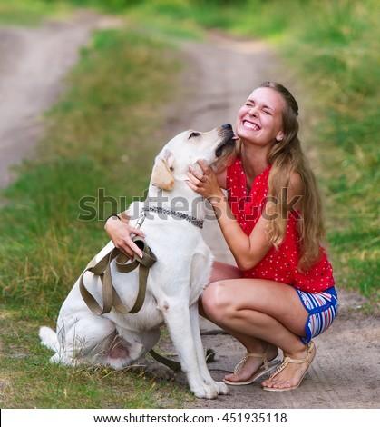 Charming girl and dog. Dog of breed Labrador. - stock photo