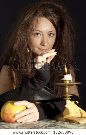 Charming girl as a witch on a dark background - stock photo