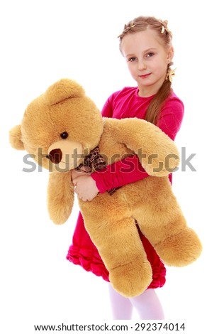 Charming girl children love hugging a big Teddy bear, close-up - isolated on white background - stock photo