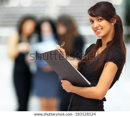 Charming girl holding a folder and looking at camera with a smile - stock photo