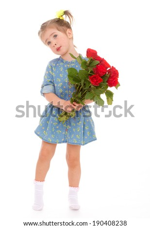 Charming girl in blue dress with a bouquet of red roses
