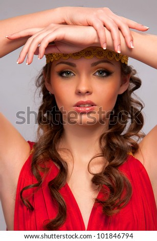 Charming girl in the red dress on an gray background - stock photo