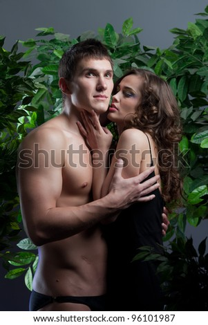 charming girl kissing a young man among the green trees