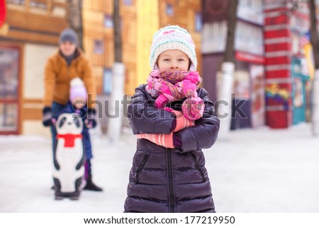 Charming girl on skating rink, dad with little sister in the background - stock photo
