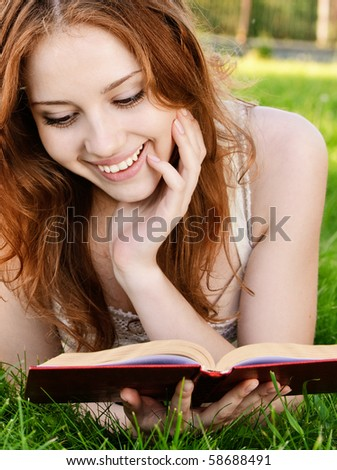 Charming girl reads book on green grass. - stock photo