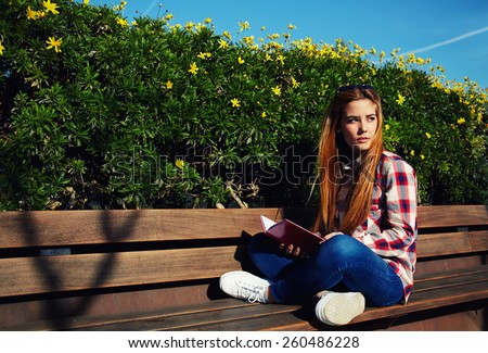 Charming girl relaxing in the spring park while read book, female student sitting on wooden bench at campus, attractive blonde hair young woman enjoying the sun at beautiful day outdoors - stock photo