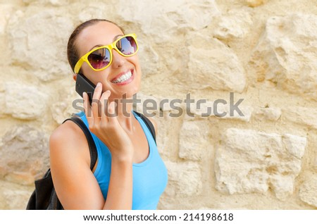 Charming girl traveler in yellow sunglass speaks by phone - stock photo
