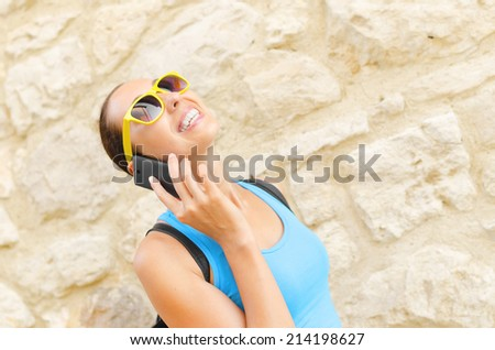 Charming girl traveler in yellow sunglass speaks by phone