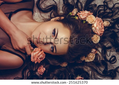 charming girl with a flowers. young woman has a beautiful face. girl lying with her long hair