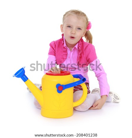 Charming girl with a yellow garden watering.kindergarten, the concept of childhood and joy, teens - stock photo