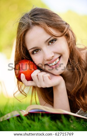 Charming girl with apple lies on green grass and reads book.