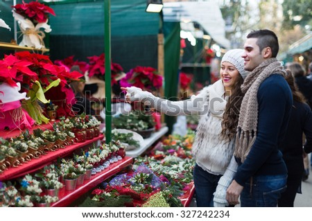 Charming girl with boyfriend choosing red flower at Christmas fair. Focus on girl - stock photo