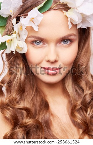 Charming girl with fresh flowers in hair - stock photo