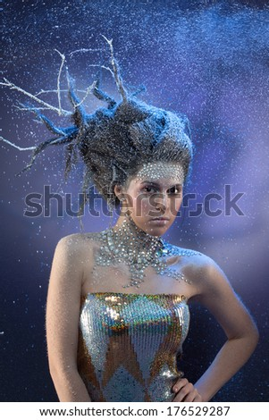 Charming girl with shining winter make up and hairstyle represents blizzards, cold and snowstorm