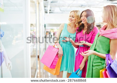 Charming girls with paperbags discussing lingerie in the shop window - stock photo