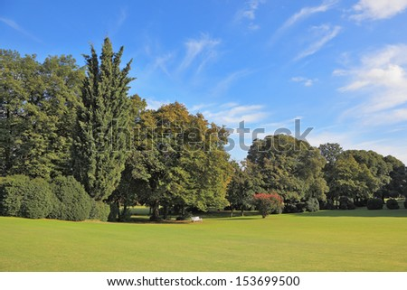 Charming green grassy lawn. The magnificent park in northern Italy in the beautiful summer day