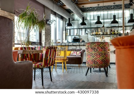 Charming hall in a loft style in a mexican restaurant with open kitchen on the background. In front of the kitchen there are wooden tables with multi-colored chairs and sofas. On the sofas there are - stock photo