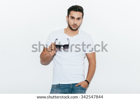 Charming handsome. Handsome young Indian man carrying sunglasses and looking at camera while standing against white background - stock photo