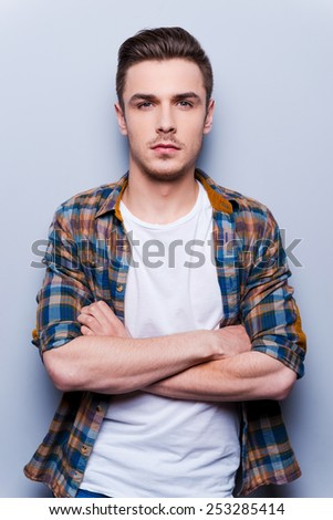 CHarming handsome. Handsome young man in shirt looking at camera and keeping arms crossed while standing against grey background  - stock photo