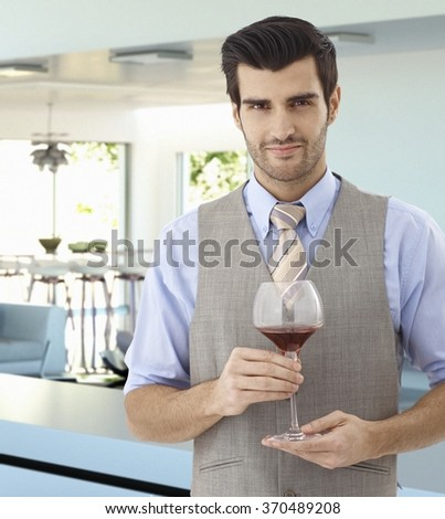 Charming handsome young caucasian man with glass of wine in hand standing indoors. Wearing suit and tie, smiling, looking at camera. - stock photo