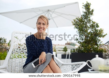 Charming happy businesswoman is holding mobile phone and looking at the camera, while is sitting in cafe terrace. Smiling female is resting after cell telephone conversation during her recreation time - stock photo