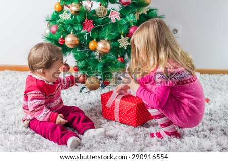 Charming happy children open Christmas presents on the floor and tree with New Year decoration at home.
