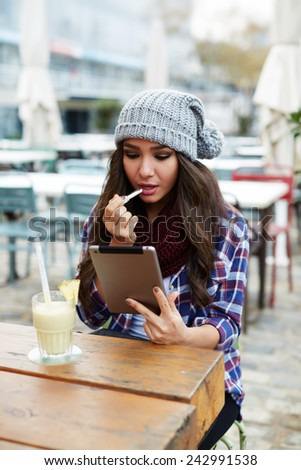 Charming hipster girl rouge lips with pink color sitting in coffee shop, woman applying lipstick outdoors - stock photo